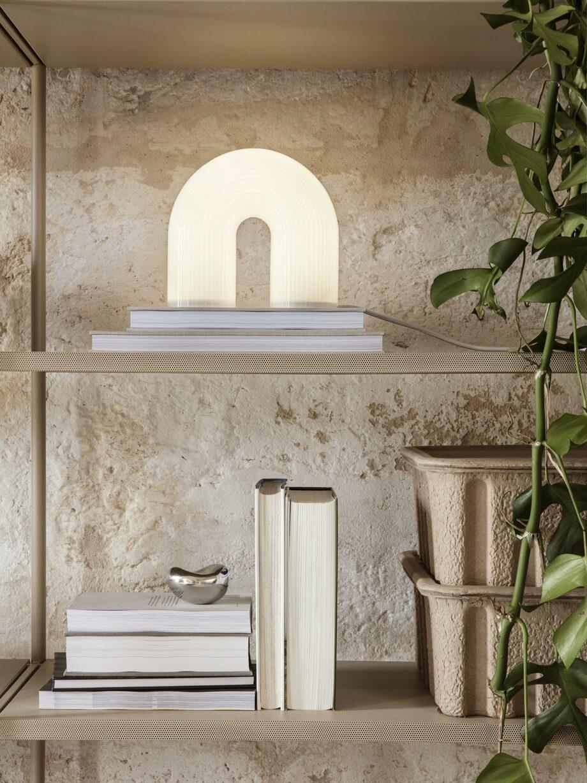 Vuelta boogvormige tafellamp van Ferm Lving in wit opaalglas op een kast